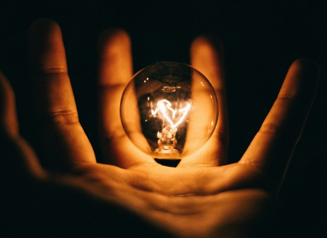 Image of a a lit bulb in a person's hand